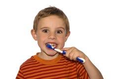 Dientes que aplican con brocha del niño Imagenes de archivo
