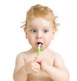 Dientes que aplican con brocha del niño aislados en blanco Imagen de archivo