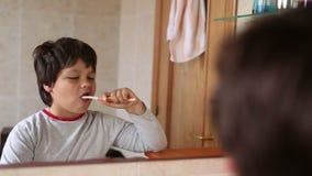 Dientes que aplican con brocha del niño pequeño almacen de metraje de vídeo