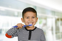 Dientes que aplican con brocha del niño Foto de archivo libre de regalías