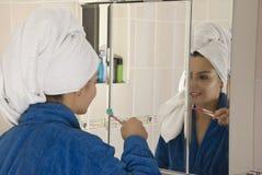 Dientes que aplican con brocha en cuarto de baño Fotografía de archivo libre de regalías