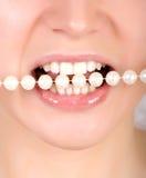 Dientes que muerden en las perlas de faux Foto de archivo libre de regalías