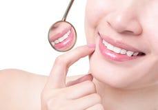 Dientes sanos de la mujer y un espejo de boca del dentista Foto de archivo libre de regalías