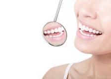 Dientes sanos de la mujer y un espejo de boca del dentista Foto de archivo