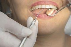 Dientes sanos de la mujer y un espejo de boca del dentista Imágenes de archivo libres de regalías
