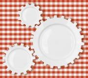 Dientes y placas de los engranajes sobre mantel rojo de la comida campestre Imagenes de archivo