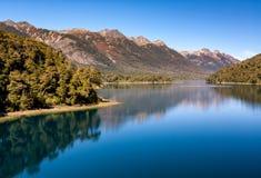 Diep blauw meer die op hemel en vegetatie wijzen bergen in de rug stock afbeelding