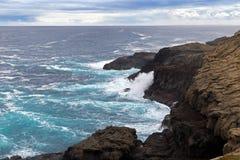 Diep blauw zeewater die vulkanische rots bij gietgallen, Kaap B bespatten stock fotografie