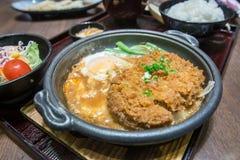 Diep In brand gestoken varkensvlees dat met verse eibovenkant wordt gekookt op de rijstkom stock afbeelding
