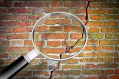 Diepe barst in oude bakstenen muur met vergrootglas - conceptenbeeld stock foto