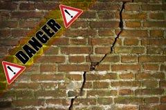 Diepe barst in oude beschadigde vochtige die bakstenen muur - conceptenbeeld met gevaarstekst op het wordt geschreven stock foto