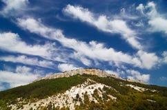 Diepe blauwe hemel en wolken over de bergen Stock Foto's