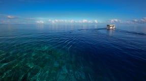 Diepe blauwe oceaan en boot Stock Afbeeldingen