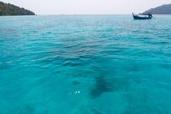 Diepe blauwe oceaan met boot Stock Foto's