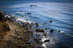 Diepe blauwe oceaankustlijn met rotsachtige kust Stock Afbeeldingen