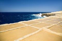 Diepe blauwe overzees, horizon en hemel met geel-bruine de kustvoorgrond van de zandsteen Zoute vijvers in Gozo-eiland, Malta royalty-vrije stock fotografie