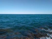 Diepe blauwe overzeese 12 66 4000 01 achtergrond over blauwe hemel Royalty-vrije Stock Foto's