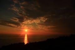 Diepe oranje zon met bezinning Stock Fotografie