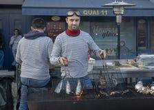 DIEPPE, ΓΑΛΛΊΑ - 17 ΝΟΕΜΒΡΊΟΥ 2018: Το άτομο μαγειρεύει τις ρέγγες στη σχάρα Δίκαιο κοχύλι ρεγγών και οστράκων στην αγορά στοκ φωτογραφία με δικαίωμα ελεύθερης χρήσης