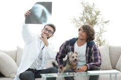 Dierenarts die een röntgenstraal tonen aan de eigenaar van de hond stock foto's