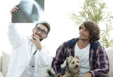 Dierenarts die een röntgenstraal tonen aan de eigenaar van de hond royalty-vrije stock afbeelding
