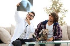 Dierenarts die een röntgenstraal tonen aan de eigenaar van de hond royalty-vrije stock foto