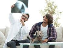 Dierenarts die een röntgenstraal tonen aan de eigenaar van de hond stock fotografie