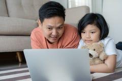 Diese asiatische Familie hat Vater und Tochter Ein kleines Mädchen und ein Vater betrachten Laptop, den sie in ihrem Haus glückli lizenzfreie stockfotografie