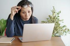 Diese asiatische Frau arbeitet an Laptop im Büro Auf ihrem Gesicht sind Ausdrucküberraschung und glückliches zum Joberfolg lizenzfreies stockfoto