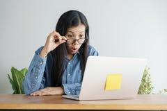 Diese asiatische Frau arbeitet an Laptop im Büro Auf ihrem Gesicht sind Ausdrucküberraschung und glückliches zum Joberfolg stockbild