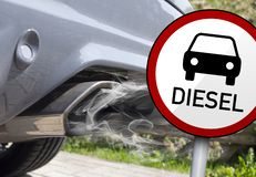 Diesel ban and diesel manupilation in germany. Road sign in front of an exhaust, Diesel ban and diesel manupilation in germany royalty free stock photography