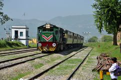 Diesel electric train locomotive speeds past student. Pakistan Railways Awam Express (down) train on its way to Karachi travels through the Golra Sharif station Royalty Free Stock Photos