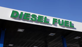 Diesel Fuel Sign. Above pumps at gas station with green letters on white background against blue sky above stock photos