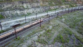 Diesel locomotive is pushing dump-car filled with rubble stone in the background of a quarry for limestone mining stock footage