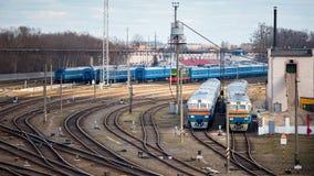 Diesel- lokomotiv och vagnar står i bussgarage med massor av stånggafflar och stänger i solig vårdag royaltyfri fotografi