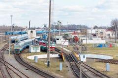 Diesel- lokomotiv och vagnar står i bussgarage nära järnväg skivtallrik royaltyfri foto