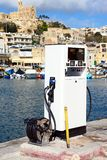 Diesel pump in Mgarr harbour, Gozo. Diesel pump on the quayside with traditional fishing boats in the harbour and the Our Lady of Lourdes church on the hillside Stock Image