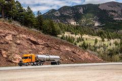 Diesel semi trailer truck on highway in rocky mountains. Orange diesel semi trailer truck transporting fuel down a highway in the rocky mountains royalty free stock image