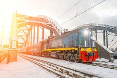 Diesel shunting locomotive overtakes passenger cars through the railway bridge in winter snow. Diesel shunting locomotive overtakes passenger cars through the Royalty Free Stock Photography
