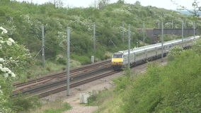 Diesel train travailing through a cutting. Diesel train travailing  through a cutting on the main London to Scotland railway line stock footage