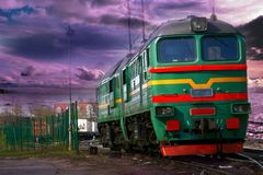 Diesel Train in the vannila sky. Freight locomotive on Latvian industrial railways in beautiful sunset. Vanilla clouds in the sky royalty free stock photo