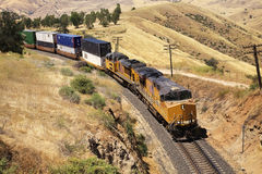 Diesel trains are transporting cargo containers. Cargo ship going in a scene near Royalty Free Stock Image