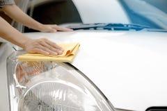 Dieses Bild ist ein Bild des Abwischens des Autos mit einem gelben microfiber Stoff durch Hände Lizenzfreie Stockfotografie
