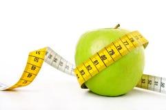 Зеленое яблоко с измеряя лентой стоковое изображение rf