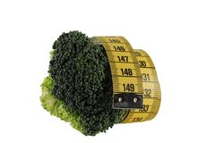 On diet. Broccoli with a metre-stick on a white background royalty free stock image