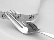 Diet. Steel fork with measuring tape Royalty Free Stock Photography