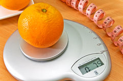 Diet. Orange on a electronic scales for weighing Stock Photography