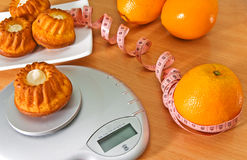 Diet. Cupcake on a electronic scales and orange with measuring tape Stock Photos