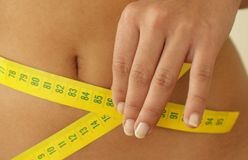 Diet. A woman holding a measuring tape around her waist Royalty Free Stock Photography