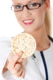 Diet. Beautiful blond female doctor holding rice cake (diet concept), isolated on white Stock Images